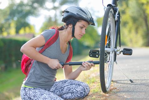 自転車に空気を入れる女性